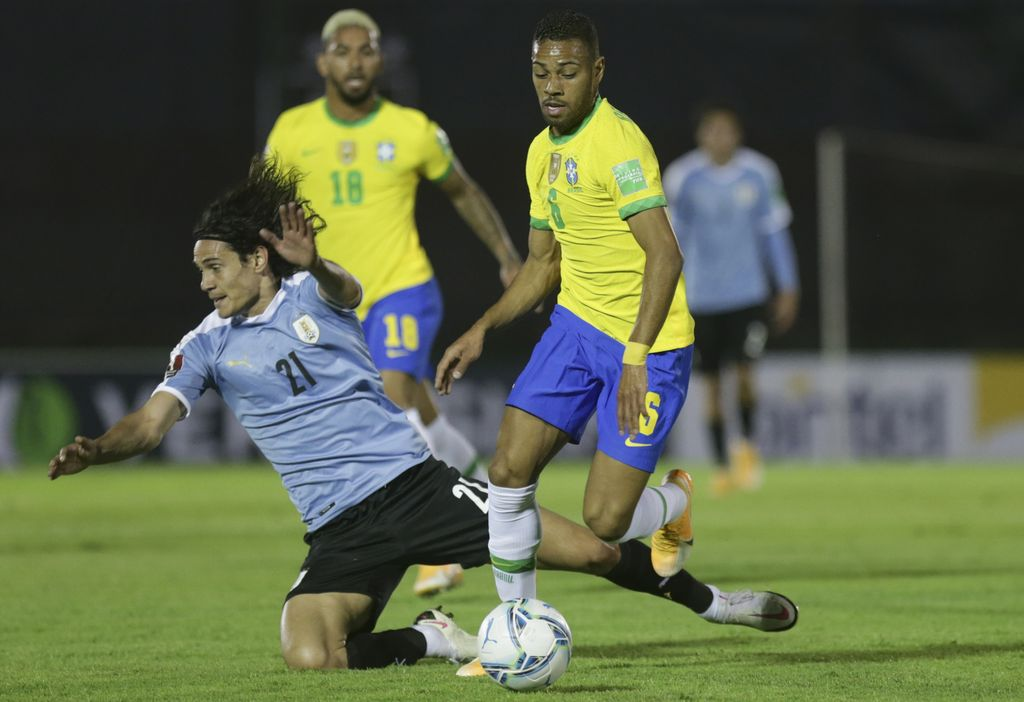Brazil's Renan Lodi, right, and Uruguay's Edinson Cavani battle for the ball during a qualifying soccer match for the FIFA World Cup Qatar 2022 at the Centenario stadium In Montevideo, Uruguay, Tuesday, Nov. 17, 2020. (AP Photo/Matilde Campodonico, Pool)