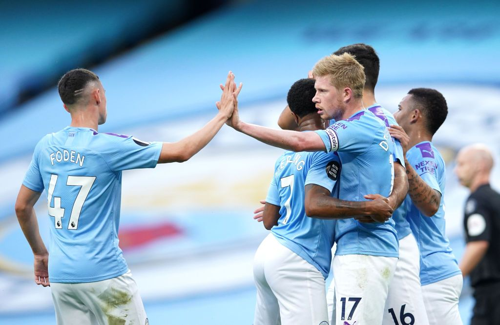 MANCHESTER, ENGLAND - JULY 02: Kevin De Bruyne of Manchester City celebrates with Raheem Sterling and Phil Foden after scoring his team's first goal during the Premier League match between Manchester City and Liverpool FC at Etihad Stadium on July 02, 2020 in Manchester, England. Football Stadiums around Europe remain empty due to the Coronavirus Pandemic as Government social distancing laws prohibit fans inside venues resulting in all fixtures being played behind closed doors. (Photo by Dave Thompson/Pool via Getty Images)