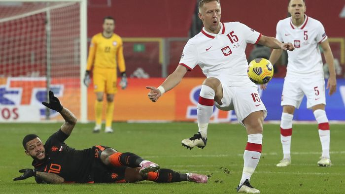 Polands Kamil Glik, center, and Netherlands Memphis Depay, left, vie for the ball during the Nations League soccer match between Poland and The Netherlands at Silesian Stadium in Chorzow, Poland, Wednesday, Nov. 18, 2020. (AP Photo/Czarek Sokolowski)