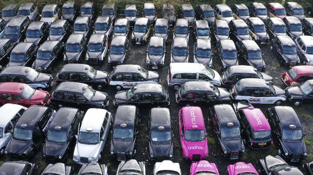 An aerial view shows black London taxi cabs parked up in a field in Epping, north-east of London on November 19, 2020. - Picking up a fare has become so hard for London's legendary black cabs that many taxis are being mothballed. Some taxi drivers who hire their cabs have returned them to fleet companies, which are then forced to store the vehicles in fields around the city. (Photo by Will EDWARDS / AFP) / TO GO WITH AFP STORY BY ANNA MALPAS