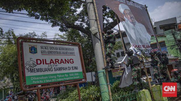 Sejumlah anggota TNI melakukan pencopotan baliho bergambar Rizieq Shihab di kawasan Petamburan, Jakarta, Jumat, 20 November 2020. Pangdam Jaya Mayjen TNI Dudung Abdurachman menyatakan pihaknya bakal mencopot semua baliho pentolan Front Pembela Islam (FPI) Rizieq Shihab yang terpasang sembarangan dan tanpa izin. CNN Indonesia/Bisma Septalisma