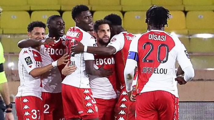 Monacos Spanish midfielder Cesc Fabregas (C) celebrates with teammates after scoring a penalty kickduring the French L1 football match between Monaco (ASM) and Paris Saint-Germain (PSG) at the Louis II Stadium in Monaco on November 20, 2020. (Photo by Valery HACHE / AFP)
