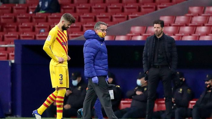 MADRID, SPAIN - NOVEMBER 21: Diego Simeone, Head Coach of Atletico de Madrid looks on as Gerard Pique of FC Barcelona looks dejected following his teams defeat in the La Liga Santander match between Atletico de Madrid and FC Barcelona at Estadio Wanda Metropolitano on November 21, 2020 in Madrid, Spain. Football Stadiums around Europe remain empty due to the Coronavirus Pandemic as Government social distancing laws prohibit fans inside venues resulting in fixtures being played behind closed doors. (Photo by Gonzalo Arroyo Moreno/Getty Images)