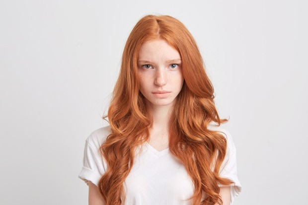 closeup-beautiful-redhead-young-woman-with-wavy-long-hair-freckles-wears-t-shirt-feels-sad-looks-front-isolated-white-wall_295783-945