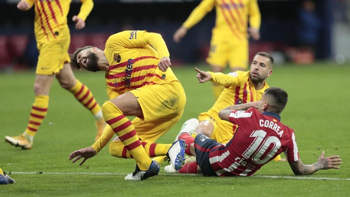 Barcelonas Gerard Pique, left, reacts after getting an injury in a challenge with Atletico Madrids Angel Correa during the Spanish La Liga soccer match between Atletico Madrid and FC Barcelona at the Wanda Metropolitano stadium in Madrid, Spain, Saturday, Nov. 21, 2020. (AP Photo/Bernat Armangue)