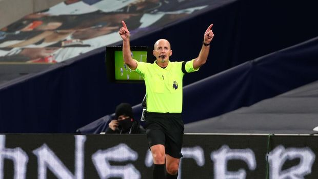 LONDON, ENGLAND - NOVEMBER 21: Referee Mike Dean indicates that he has made his decision following a VAR pitch side check, he then goes on to disallow a goal from Manchester City due to hand ball during the Premier League match between Tottenham Hotspur and Manchester City at Tottenham Hotspur Stadium on November 21, 2020 in London, England. Sporting stadiums around the UK remain under strict restrictions due to the Coronavirus Pandemic as Government social distancing laws prohibit fans inside venues resulting in games being played behind closed doors. (Photo by Clive Rose/Getty Images)