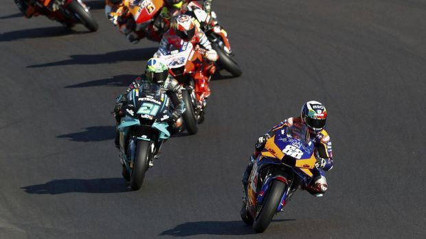 MotoGP rider Miguel Oliveira of Portugal steers his motorcycle ahead of Franco Morbidelli of Italy and Jack Miller of Australia during the MotoGP race of the Portuguese Motorcycle Grand Prix, the last race of the season, at the Algarve International circuit near Portimao, Portugal, Sunday, Nov. 22, 2020. (AP Photo/Armando Franca)