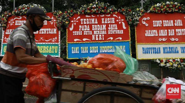 Masyarakat berswa foto dan menggambil gambar karangan bunga yang bernarasi positif untuk memberikan dukungan kepada TNI dan Polri. Jakarta. Senin (23/11/2020). Ratusan jajaran karangan bunga memenuhi tepi jalan di depan markas Kodam Jaya. CNN Indonesia/Andry Novelino