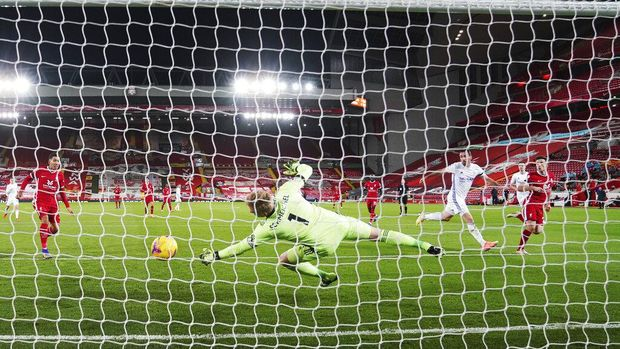 Liverpool's Diogo Jota, right, scores his sides second goal past Leicester's goalkeeper Kasper Schmeichel, center, during the English Premier League soccer match between Liverpool and Leicester City at Anfield stadium in Liverpool, England, Sunday, Nov. 22, 2020. (AP Photo/Jon Super)