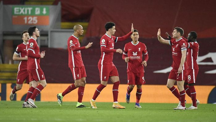 Liverpools team players celebrate after Leicesters Jonny Evans scored an own goal during the English Premier League soccer match between Liverpool and Leicester City at Anfield stadium in Liverpool, England, Sunday, Nov. 22, 2020. (Peter Powell/Pool via AP)