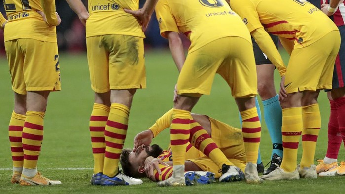 Barcelonas Gerard Pique, bottom, reacts after getting an injury during the Spanish La Liga soccer match between Atletico Madrid and FC Barcelona at the Wanda Metropolitano stadium in Madrid, Spain, Saturday, Nov. 21, 2020. (AP Photo/Bernat Armangue)