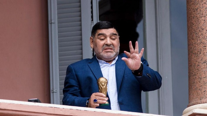 BUENOS AIRES, ARGENTINA - DECEMBER 26: Former Argentinian legend and current coach of Gimnasia y Esgrima La Plata Diego Maradona gestures with a small replica of the FIFA World Cup trophy at the balcony of Government house after a meeting with President of Argentina Alberto Fernandez at Casa Rosada on December 26, 2019 in Buenos Aires, Argentina. (Photo by Ricardo Ceppi/Getty Images)