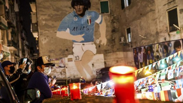 People light candles to honor Diego Maradona, in Naples, Italy, Wednesday, Nov. 25, 2020. Diego Maradona has died. The Argentine soccer great was among the best players ever and who led his country to the 1986 World Cup title before later struggling with cocaine use and obesity. He was 60. (Alessandro Garofalo/LaPresse via AP)
