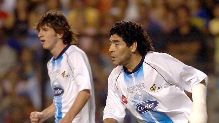 Argentine former football legend Diego Maradona (R) and Lionel Messi run during the friendly match