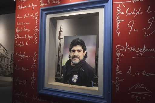 An employee prepares to place a picture of late Argentinian football legend Diego Armando Maradona at Mother's Wax Museum before the start of an event for Maradona fans to pay their respects, in Kolkata on November 26, 2020. - Maradona passed away on November 25, 2020. (Photo by Dibyangshu SARKAR / AFP)