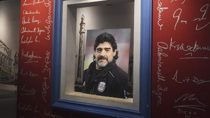 An employee prepares to place a picture of late Argentinian football legend Diego Armando Maradona at Mothers Wax Museum before the start of an event for Maradona fans to pay their respects, in Kolkata on November 26, 2020. - Maradona passed away on November 25, 2020. (Photo by Dibyangshu SARKAR / AFP)