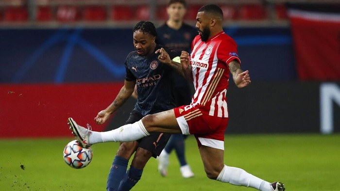 Manchester Citys Raheem Sterling , left, fights for the ball with Olympiacos Yann MVila During the Champions League, group C soccer match between Olympiacos and Manchester City at Georgios Karaiskakis stadium in Piraeus port, near Athens, Wednesday, Nov. 25, 2020. (AP Photo/Thanassis Stavrakis)