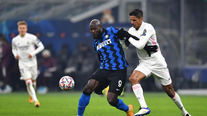 MILAN, ITALY - NOVEMBER 25: Romelu Lukaku of Inter Milan is challenged by Raphael Varane of Real Madrid during the UEFA Champions League Group B stage match between FC Internazionale and Real Madrid at Stadio Giuseppe Meazza on November 25, 2020 in Milan, Italy. Football Stadiums around Europe remain empty due to the Coronavirus Pandemic as Government social distancing laws prohibit fans inside venues resulting in fixtures being played behind closed doors. (Photo by Valerio Pennicino/Getty Images)