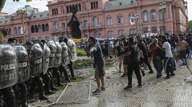 Soccer fans waiting to attend the wake for Diego Maradona face off police outside the presidential palace in Buenos Aires, Argentina, Thursday, Nov. 26, 2020. The Argentine soccer great who led his country to the 1986 World Cup title, died Wednesday at the age of 60. (AP Photo/Rodrigo Abd)