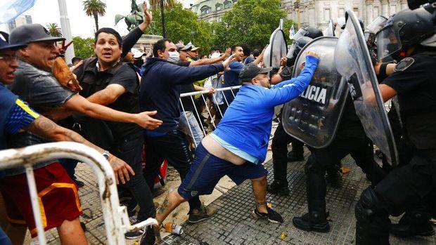 Warga tumpah ruah memadati halaman Istana Presiden Argentina. Kedatangan mereka untuk berikan penghormatan terakhir bagi Maradona yang disemayamkan di sana.