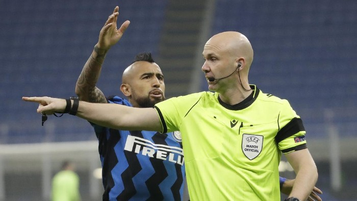 Inter Milans Arturo Vidal, left, argues with referee Anthony Taylor during the Group B, Champions League soccer match between Inter Milan and Real Madrid at the San Siro Stadium, in Milan, Italy, Wednesday, Nov. 25, 2020. (AP Photo/Luca Bruno)