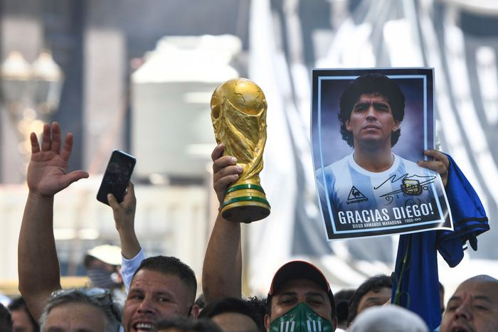 BUENOS AIRES, ARGENTINA - NOVEMBER 26:  A fans holds a photograph of Diego Maradona and a replica of the world cup trophy as he queues to enter the government palace on November 26, 2020 in Buenos Aires, Argentina. Maradona died of a heart attack at his home on Thursday 25 aged 60 . He is considered among the best footballers in history and lead his national team to the World Cup in 1986. President of Argentina Alberto Fernandez declared three days of national mourning. (Photo by Rodrigo Valle/Getty Images)