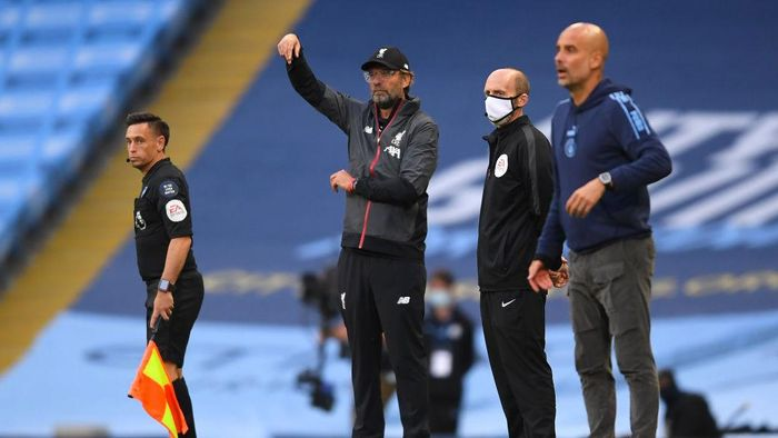 MANCHESTER, ENGLAND - JULY 02: Jurgen Klopp, Manager of Liverpool gives his team instructions as Pep Guardiola, Manager of Manchester City looks on during the Premier League match between Manchester City and Liverpool FC at Etihad Stadium on July 02, 2020 in Manchester, England. Football Stadiums around Europe remain empty due to the Coronavirus Pandemic as Government social distancing laws prohibit fans inside venues resulting in all fixtures being played behind closed doors. (Photo by Laurence Griffiths/Getty Images)