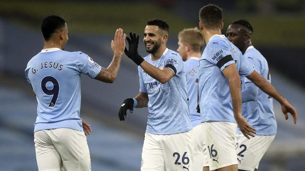 Manchester City's Riyad Mahrez, centre, celebrates with teammates after scoring his side's second goal during the English Premier League soccer match between Manchester City and Burnley at the Etihad stadium in Manchester, England, Saturday, Nov. 28, 2020. (Martin Rickett/Pool via AP)