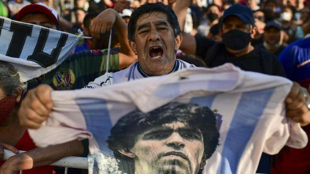 Fans gather outside the morgue where the late Argentine football star Diego Maradona's body will undergo an autopsy