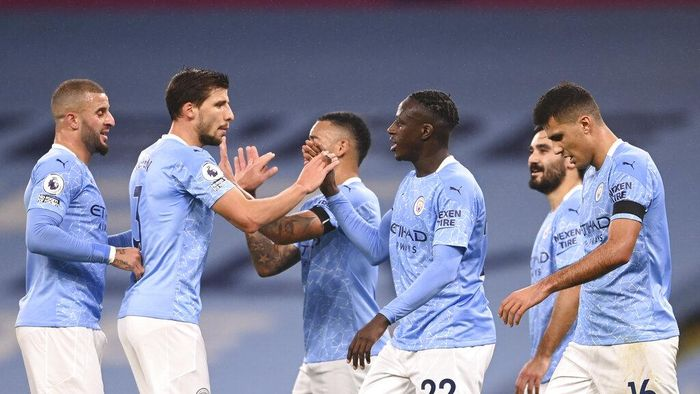 Manchester Citys Benjamin Mendy celebrates with teammates after scoring his sides third goal during the English Premier League soccer match between Manchester City and Burnley at the Etihad stadium in Manchester, England, Saturday, Nov. 28, 2020. (Laurence Griffiths/Pool via AP)
