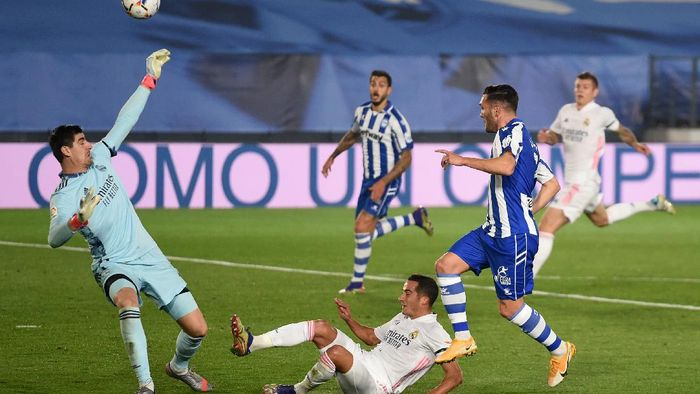 MADRID, SPAIN - NOVEMBER 28: Thibaut Courtois of Real Madrid saves a shot from Lucas of Deportivo Alaves during the La Liga Santander match between Real Madrid and Deportivo Alaves at Estadio Santiago Bernabeu on November 28, 2020 in Madrid, Spain. Football Stadiums around Europe remain empty due to the Coronavirus Pandemic as Government social distancing laws prohibit fans inside venues resulting in fixtures being played behind closed doors. (Photo by Denis Doyle/Getty Images)