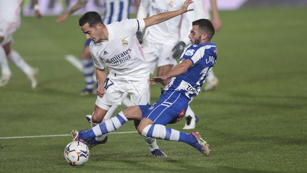 Real Madrid's Lucas Vazquez, left, is fouled by Alaves' Luis Rioja during the Spanish La Liga soccer match between Real Madrid and Alaves at Alfredo di Stefano stadium in Madrid, Spain, Saturday, Nov. 28, 2020. (AP Photo/Bernat Armangue)