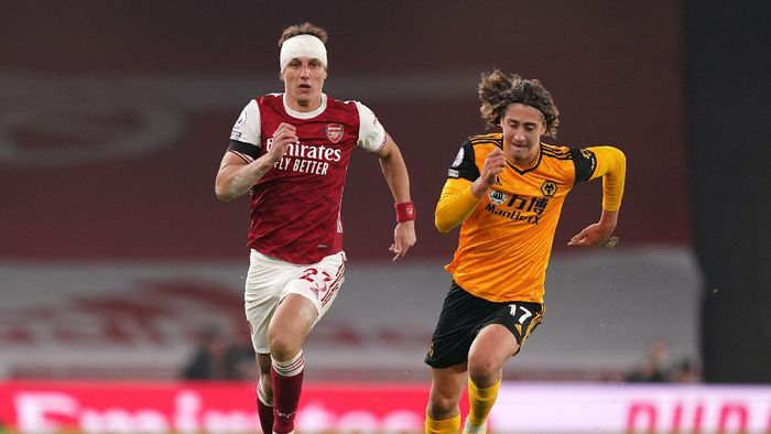 LONDON, ENGLAND - NOVEMBER 29: David Luiz of Arsenal runs with the ball whilst under pressure from Fabio Silva of Wolverhampton Wanderers during the Premier League match between Arsenal and Wolverhampton Wanderers at Emirates Stadium on November 29, 2020 in London, England. Sporting stadiums around the UK remain under strict restrictions due to the Coronavirus Pandemic as Government social distancing laws prohibit fans inside venues resulting in games being played behind closed doors. (Photo by John Walton - Pool/Getty Images)