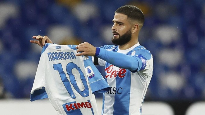 Lorenzo Insigne of Napoli holding a number 10 Maradona shirt, celebrates after scoring the first goal of the game against AS Roma, during their Serie A soccer match between Napoli and Roma, at the Naples San Paolo Stadium in Naples, Italy, Sunday, Nov. 29, 2020. (Alessandro Garofalo/LaPresse via AP)