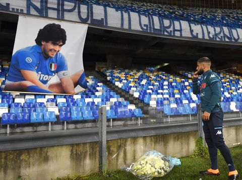 NAPLES, ITALY - NOVEMBER 29: Lorenzo Insigne of S.S.C. Napoli places tributes next to a banner showing an images of the deceased Diego Maradona during the Serie A match between SSC Napoli and AS Roma at Stadio San Paolo on November 29, 2020 in Naples, Italy. Sporting stadiums around Italy remain under strict restrictions due to the Coronavirus Pandemic as Government social distancing laws prohibit fans inside venues resulting in games being played behind closed doors. (Photo by Francesco Pecoraro/Getty Images)