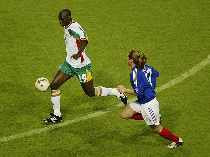 SEOUL - MAY 31:  Papa Bouba Diop (left) of Senegal is chased by Emmanuel Petit (right) of France during the France v Senegal Group A, World Cup Group  Stage match played at the Seoul World Cup Stadium, Seoul, South Korea on May 31, 2002. Senegal won the match 1-0. (Photo by Brian Bahr/Getty Images)