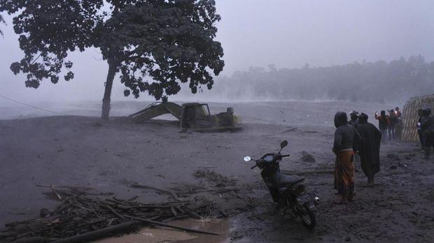 Warga melihat banjir lahar dingin Gunung Semeru di kawasan Besuk Kobokan, Pronojiwo, Lumajang, Jawa Timur, Selasa (1/12/2020). Banjir lahar dingin mengakibatkan terputusnya akses jalan antar kecamatan di Lumajang serta sejumlah truk dan alat berat penambang pasir terjebak. ANTARA FOTO/Seno/rwa.