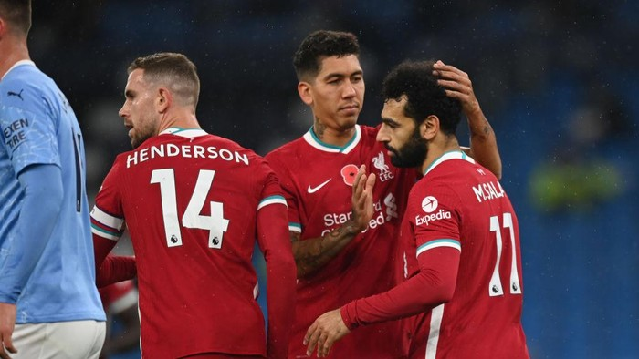 MANCHESTER, ENGLAND - NOVEMBER 08: Mohamed Salah of Liverpool celebrates with teammates Roberto Firmino and Jordan Henderson after scoring his teams first goal during the Premier League match between Manchester City and Liverpool at Etihad Stadium on November 08, 2020 in Manchester, England. Sporting stadiums around the UK remain under strict restrictions due to the Coronavirus Pandemic as Government social distancing laws prohibit fans inside venues resulting in games being played behind closed doors. (Photo by Shaun Botterill/Getty Images)