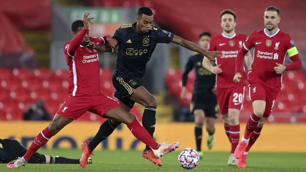 Liverpool's Georginio Wijnaldum, left, duels for the ball with Ajax's Ryan Gravenberch during the Champions League group D soccer match between Liverpool and Ajax at Anfield stadium in Liverpool, England, Tuesday, Dec. 1, 2020. (Michael Regan/Pool via AP)