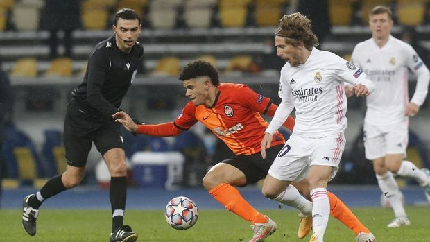 Shakhtar's Taison, centre, and Real Madrid's Luka Modric challenge for the ball during the Champions League, Group B, soccer match between Shakhtar Donetsk and Real Madrid at the Olimpiyskiy Stadium in Kyiv, Ukraine, Tuesday, Dec. 1, 2020. (AP Photo/Efrem Lukatsky)