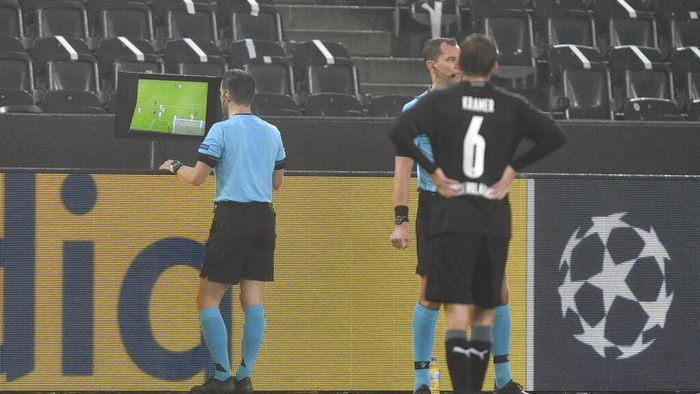Referee Danny Makkelie checks the VAR monitor during the Champions League, Group B, soccer match between Borussia Moenchengladbach and Inter Milan at the Borussia Park in Moenchengladbach, Germany, Tuesday, Dec. 1, 2020. (AP Photo/Martin Meissner)