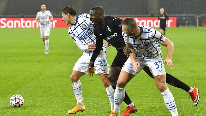Moenchengladbachs Marcus Thuram, center, is challenged by Inter Milans Nicolo Barella, left, and Inter Milans Milan Skriniar during the Champions League, Group B, soccer match between Borussia Moenchengladbach and Inter Milan at the Borussia Park in Moenchengladbach, Germany, Tuesday, Dec. 1, 2020. (AP Photo/Martin Meissner)