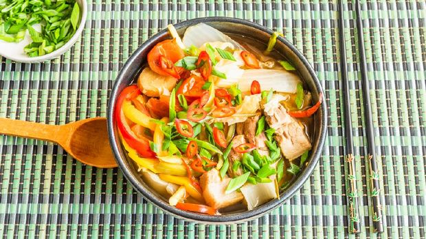 Suan cai - traditional Chinese stew of pork and pickled Chinese cabbage in a black bowl on a bamboo napkin.