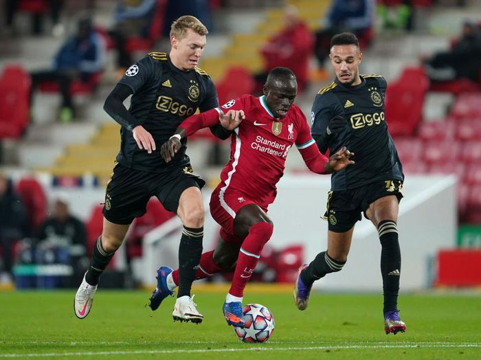 LIVERPOOL, ENGLAND - DECEMBER 01: Sadio Mane of Liverpool is challenged by Perr Schuurs and Jurgen Ekkelenkamp of Ajax during the UEFA Champions League Group D stage match between Liverpool FC and Ajax Amsterdam at Anfield on December 01, 2020 in Liverpool, England. Sporting stadiums around the UK remain under strict restrictions due to the Coronavirus Pandemic as Government social distancing laws prohibit fans inside venues resulting in games being played behind closed doors. (Photo by Jon Super - Pool/Getty Images)