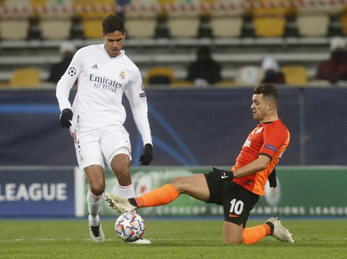 Real Madrids Raphael Varane, left, and Shakhtars Junior Moraes challenge for the ball during the Champions League, Group B, soccer match between Shakhtar Donetsk and Real Madrid at the Olimpiyskiy Stadium in Kyiv, Ukraine, Tuesday, Dec. 1, 2020. (AP Photo/Efrem Lukatsky)