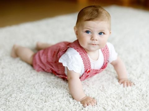 The baby was excited and delighted in the pink cloth.
