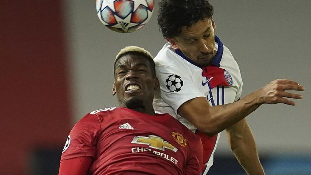 Manchester United's Paul Pogba, left and PSG's Marquinhos jump for the ball during a Group H Champions League soccer match between Manchester United and Paris Saint Germain at the Old Trafford stadium in Manchester, England, Wednesday, Dec. 2, 2020. (AP Photo/Dave Thompson)