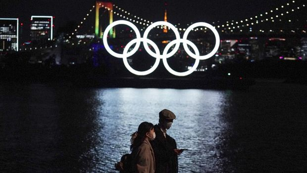 A man and a woman walk past near the Olympic rings floating in the water in the Odaiba section Tuesday, Dec. 1, 2020, in Tokyo. The Olympic Symbol was reinstalled after it was taken down for maintenance ahead of the postponed Tokyo 2020 Olympics. (AP Photo/Eugene Hoshiko)