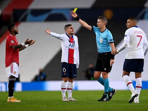 MANCHESTER, ENGLAND - DECEMBER 02: Fred of Manchester United(L) is shown a yellow card by Match Referee Daniele Orsato(2R) during the UEFA Champions League Group H stage match between Manchester United and Paris Saint-Germain at Old Trafford on December 02, 2020 in Manchester, England. Sporting stadiums around the UK remain under strict restrictions due to the Coronavirus Pandemic as Government social distancing laws prohibit fans inside venues resulting in games being played behind closed doors. (Photo by Laurence Griffiths/Getty Images)