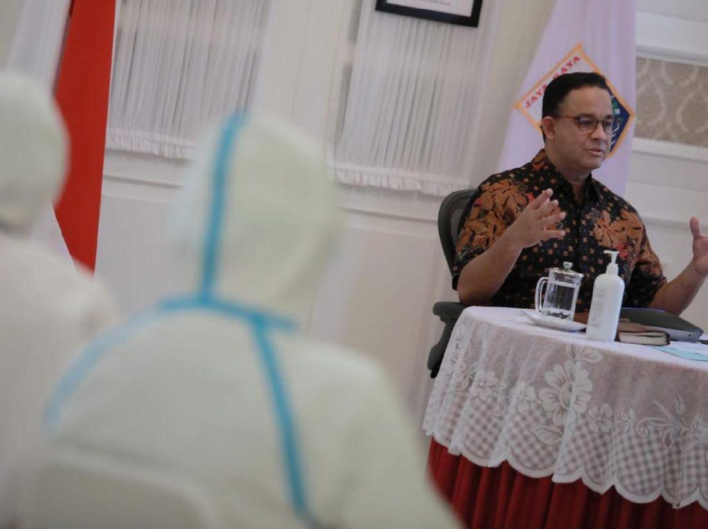 Didampingi Petugas Ber-APD, Anies Ikut Rapat Virtual dari Rumah Dinas